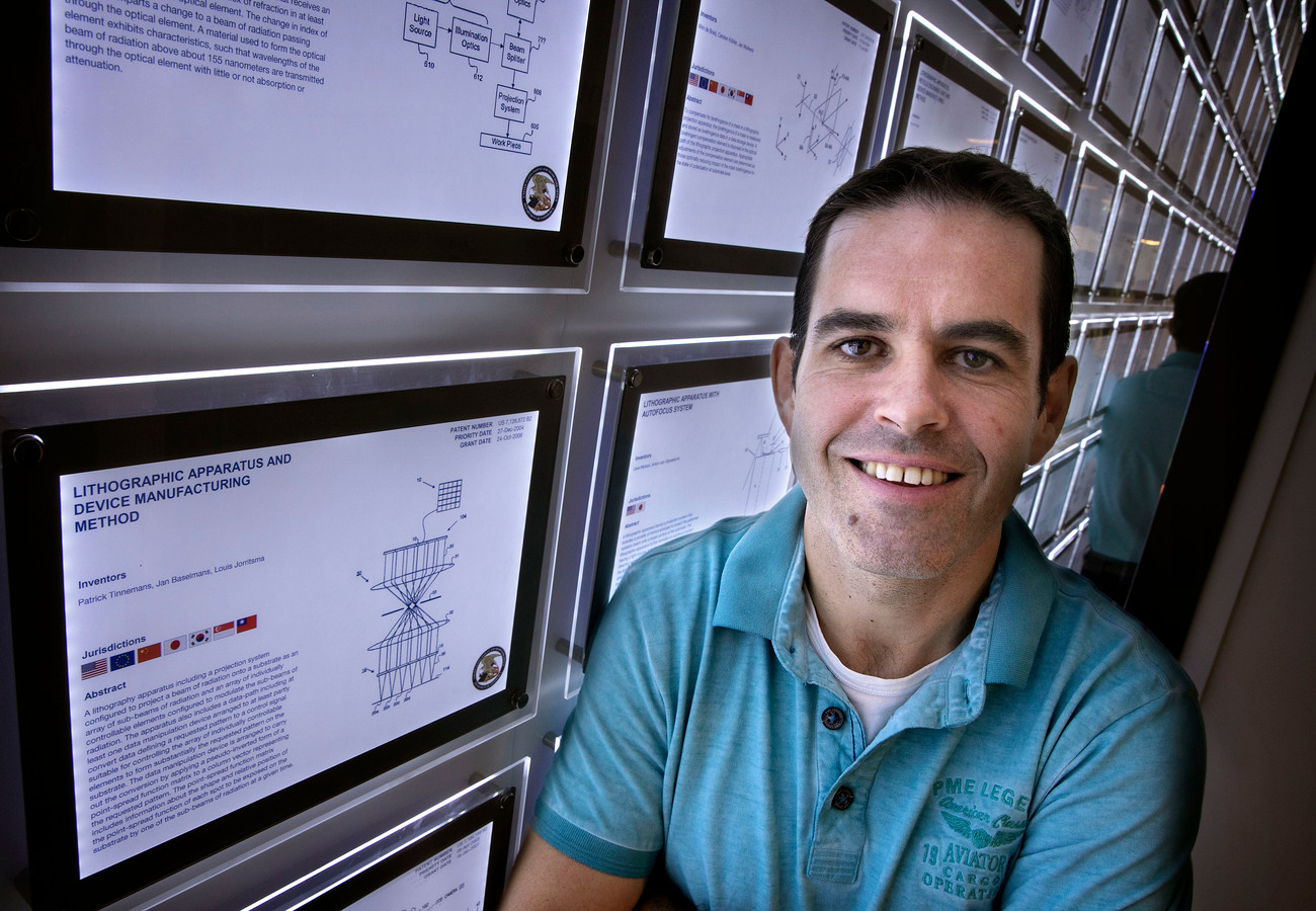 Patrick Tinnemans van ASML bij de patentenwand van ASML, waarop ook enkele van zijn patenten prijken.