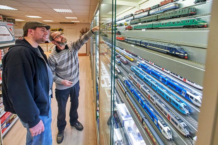 Paul Poels geeft een klant tekst en uitleg over een van de tientallen treintjes in de vitrine in Volkel.
