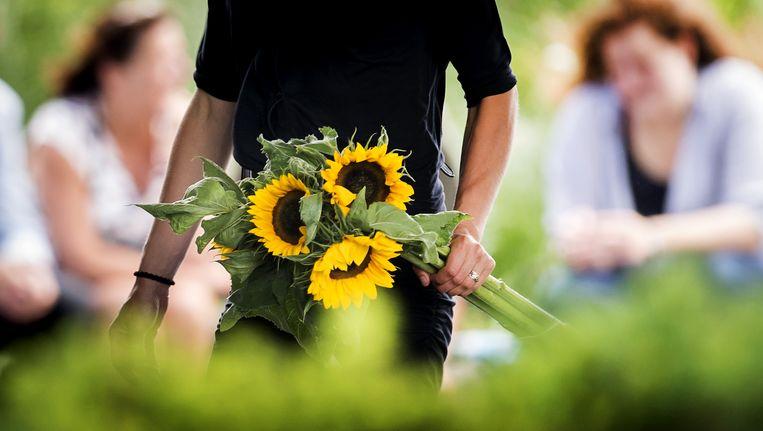 Nabestaande met zonnebloemen tijdens de MH17 herdenking in Nieuwegein. Beeld anp