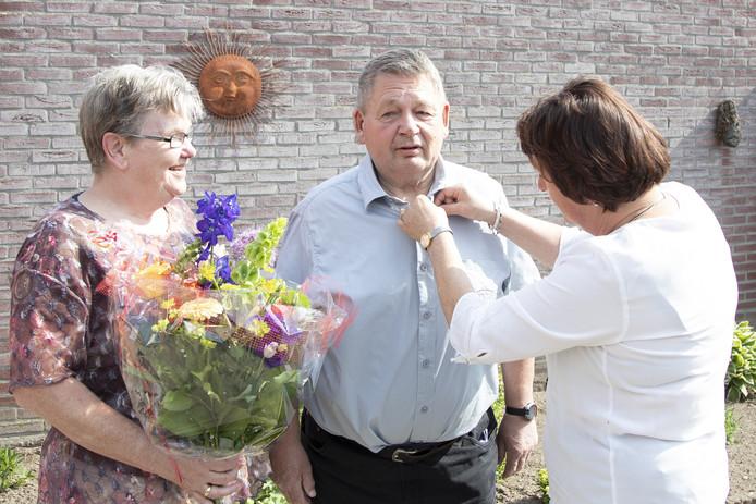 Wethouder Rosalien Slagers spelt Enternaar Bertus Brunnekreef de vrijwilligersspeld van de gemeente Wierden op.