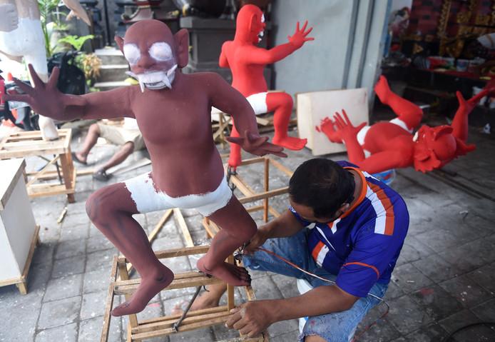 Een Balinese man werkt aan figuren die bekend staan als 'ogoh-ogoh' en het kwaad symboliseren. De poppen worden gebruikt bij de 'Day of Silence'-parade in Denpasar op Bali. Foto Sonny Tumbelaka