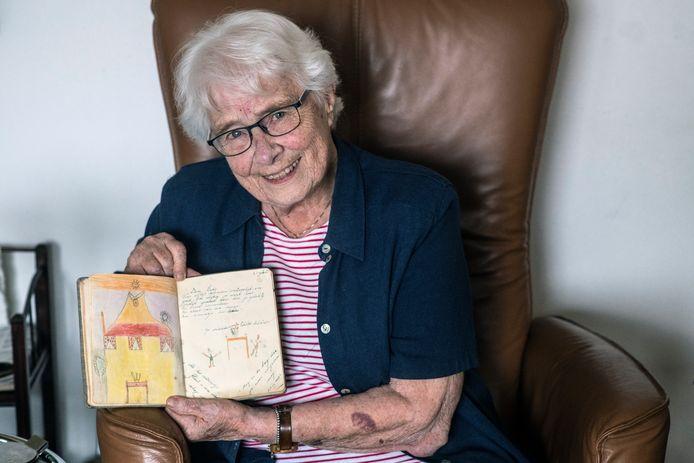 Lidy Overmeer met haar poëziealbum uit de oorlog. Op de opengeslagen bladzijden een tekening en tekst van haar Joodse vriendinnetje Edith Schöner, dat niet veel later vergast werd.