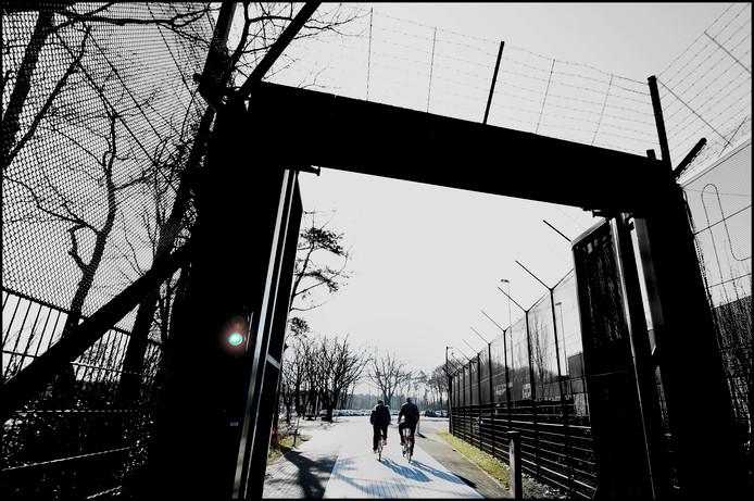 Foto ter illustratie: een patiënt en zijn begeleider verlaten per fiets de Pompekliniek om op boodschappenverlof te gaan.