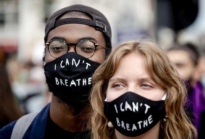 Demonstranten met een mondkapje tijdens het protest op de Dam.