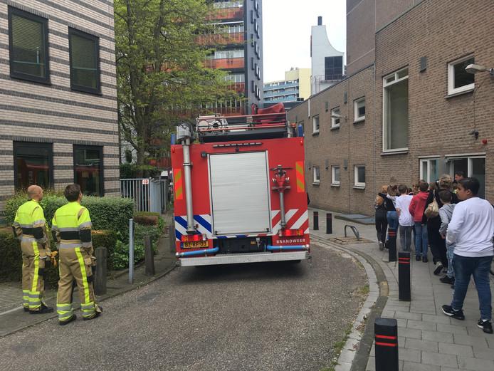 Scholieren lopen de Stadsschouwburg weer binnen, nadat de brandweer het pand heeft vrijgegeven.