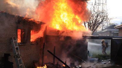 Uitslaande brand vernielt garage en tuinhuis, bewoner en brandweerman raken lichtgewond