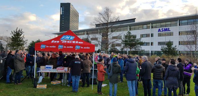 Werknemers verzamelen zich in december 2018 bij een standje van de FNV op een grasveld voor de gebouwen van ASML in Veldhoven.