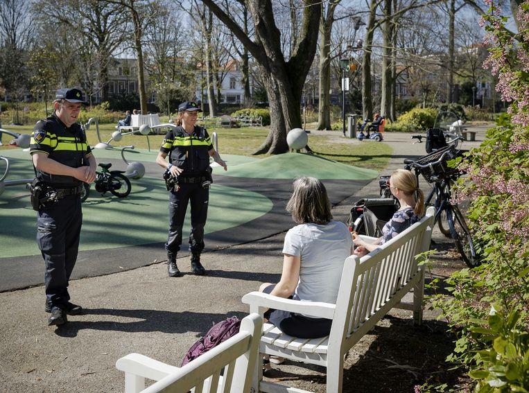 Wijkagenten controleren, op de foto in Den Haag, met het mooie weer extra goed of mensen zich houden aan de maatregelen die zijn genomen om de verspreiding van het coronavirus in te dammen.  Beeld ANP
