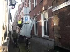 Volle vuilniscontainer valt uit hijskraan op straat en tegen appartementencomplex in Den Bosch