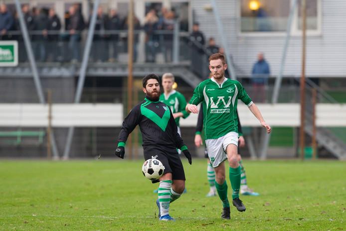Corne Hamelink (r) van Owios zet aan voor de bal.