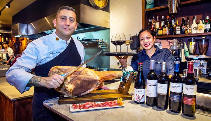 Chef Guillermo Aguirre Schicht met een jamon iberico. Rechts staat medewerkster Nicole klaar met de wijn.