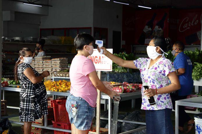 Van bezoekers van een markt in de Surinaamse hoofdstad Paramaribo wordt de temperatuur opgenomen voor zij inkopen gaan doen.