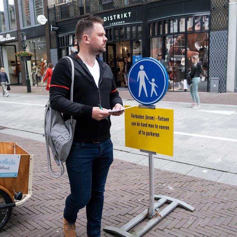 Werknemer Harold Salomons aan de slag in een van de populairste winkelstraten van Alkmaar. Beeld Sabine van Wechem