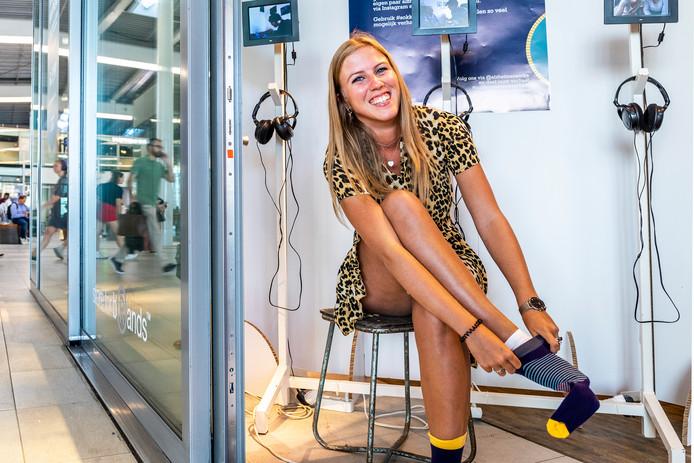Naomi van Ierland(21), de ontwerpster van de 'Alzheimer-sokken', trekt een paar aan in de speciale pop-upstore op het Centraal Station van Utrecht.
