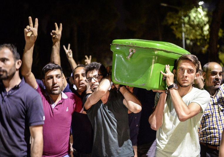 Demonstranten dragen de kist van een van de slachtoffers. Beeld anp
