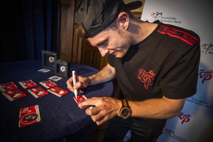 Enzo Knol signeert de eerste exemplaren van zijn eigen munt.