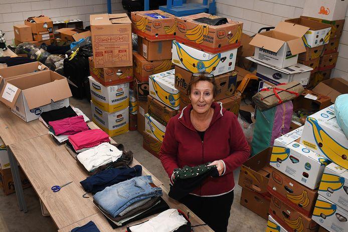 Elly Bens tussen de kleding en andere spullen in de loods van haar broer in Haps.