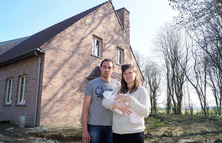 Lennert Stevens en Kimberly Vandewalle samen met de vier dagen oude Lise voor hun nieuwbouw. Als de plannen van Electrabel er door komen, hebben ze straks een windmolen van 180 meter in hun achtertuin. Van hier uit gezien zou de molen tot hoog boven de bomen in de achtertuin uittorenen.