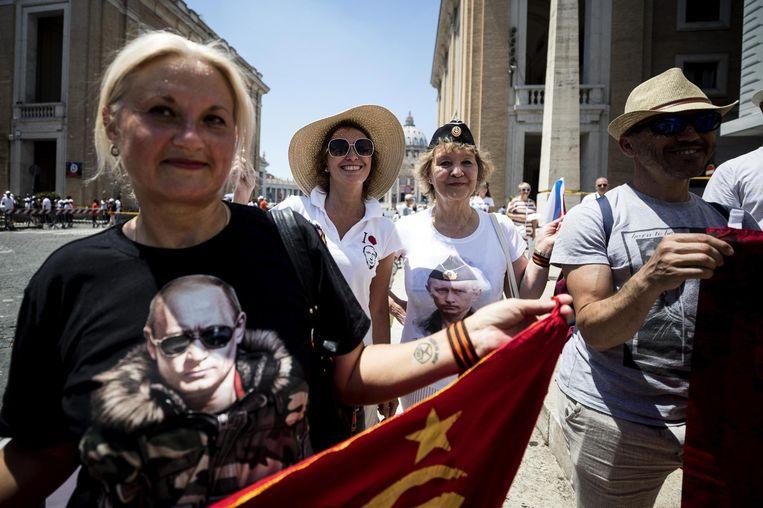 Toeristen wachten bij het Vaticaan op de komst van de Russische president Vladimir Poetin. Hij was gisteren voor een eendaags bezoek in Rome. Op zijn agenda stonden ontmoetingen met de paus en de Italiaanse politieke leiders.  Beeld EPA