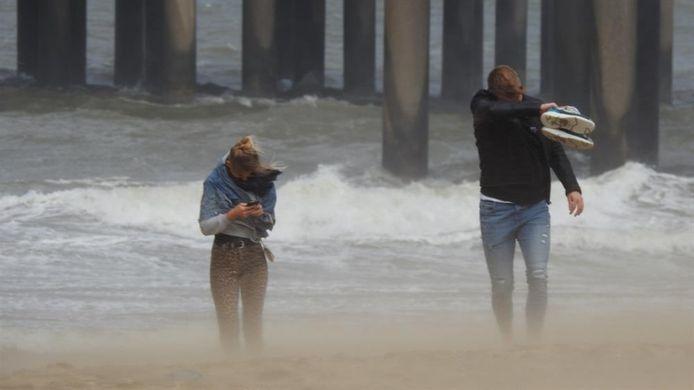 Gezandstraald worden door stormachtige wind op het strand van Scheveningen.