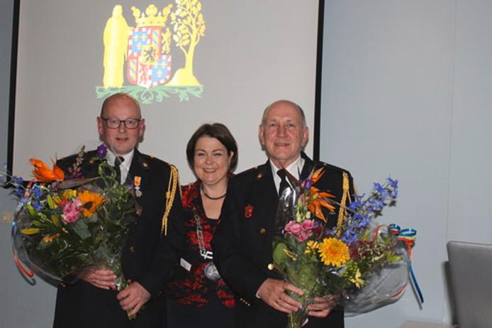 Eric van der Heijden (links) en Frans Theuws van de brandweer in Bergeijk zijn vrijdag geridderd bij hun afscheid. Burgemeester Arinda Callewaert speldde de lintjes op bij de brandweerlieden.