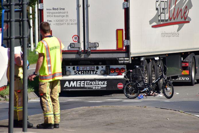 De zeventiger reed met zijn elektrische minifiets tegen de zijkant van de vrachtwagen.