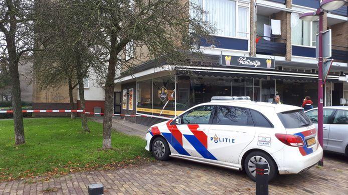 Linten zetten de ingang naar de flat af. Cafetaria Frietuurtje heeft met het incident niets van doen.