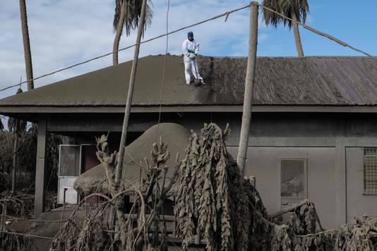 Een bewoner van het gebied rond de vulkaan veegt as van het dak van zijn woning.