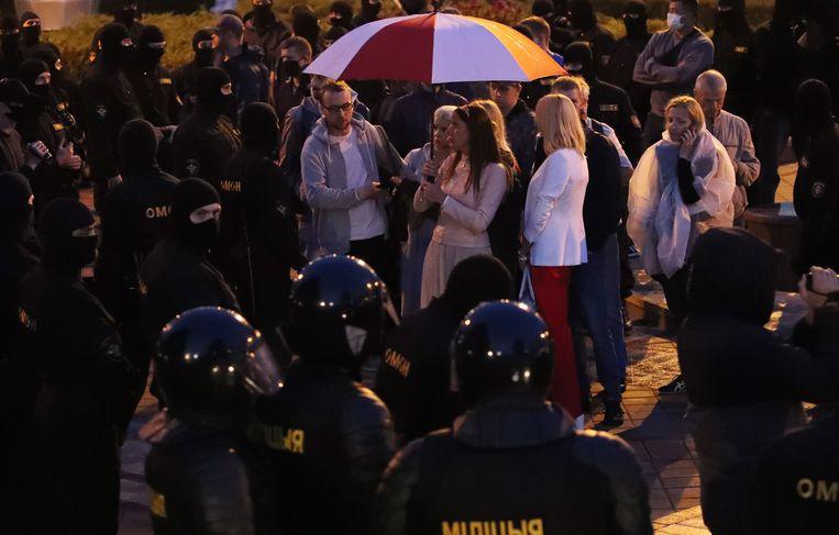 De politie omsingelt demonstranten die protesteren tegen de uitkomsten van de verkiezingen in Belarus.  Beeld EPA