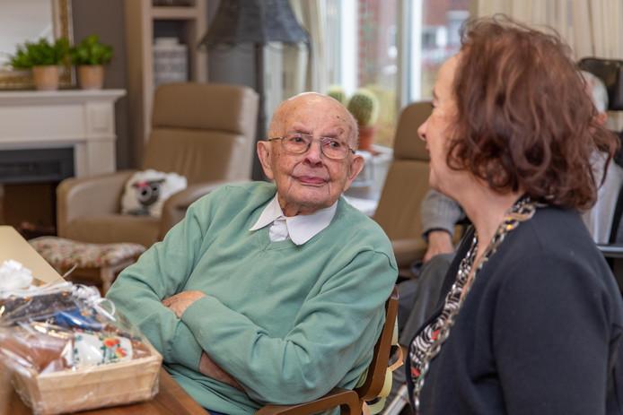 De 101-jarige Kees van Kleef luistert naar burgemeester Loes Meeuwisse, die hem de felicitaties en een cadeautje is komen brengen.