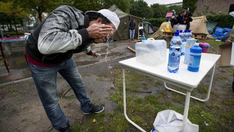 Een uitgeprocedeerde asielzoeker wast zijn gezicht bij het tentenkamp in Amsterdam Osdorp. Beeld anp