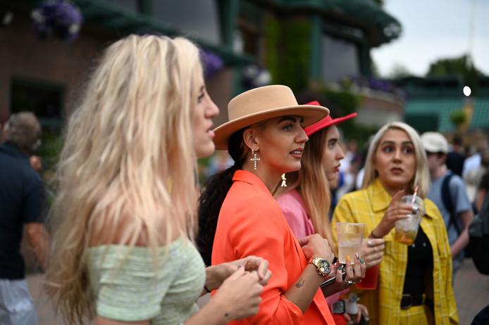 De bezoekers op Wimbledon drinken een glaasje.