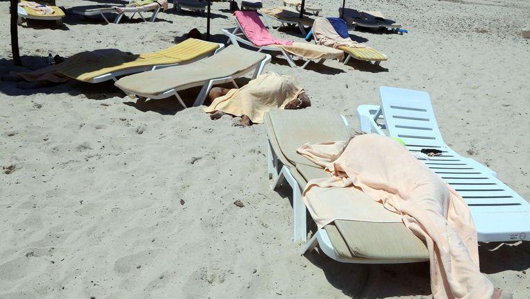 Afgedekte lichamen op het strand van Sousse, een populaire toeristische bestemming. De plaats ligt 140 kilometer van de hoofdstad Tunis. Beeld afp