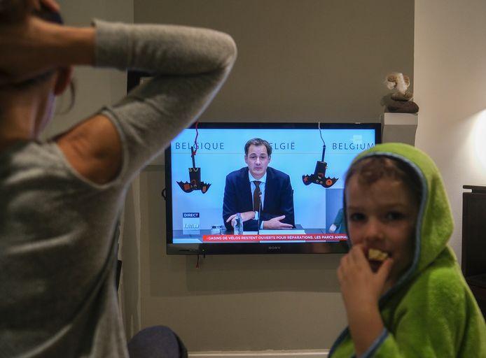 Een Belgisch gezin luistert naar premier De Croo.
