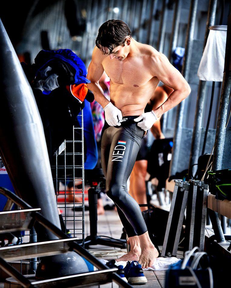 Arno Kamminga  (schoolslag zwemmer) wringt zich in allerlei bochten om het snelle zwempak aan te trekken. Beeld Klaas Jan van der Weij