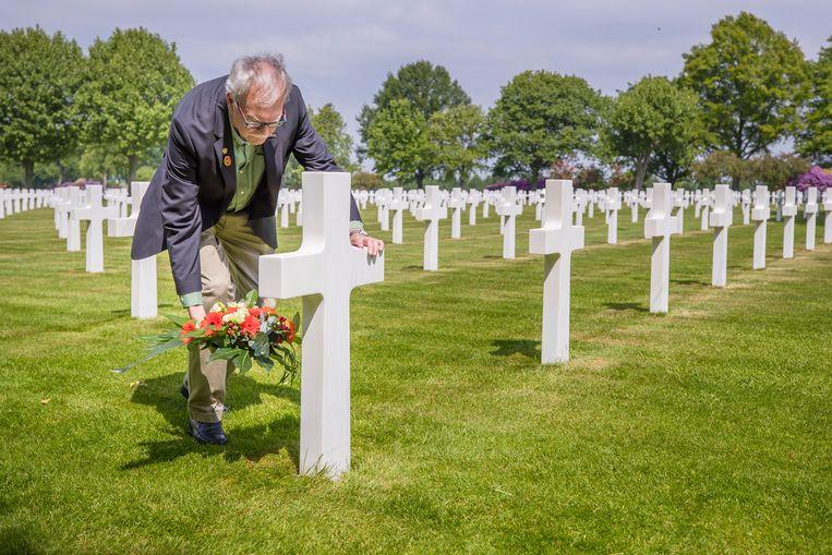 Hans Schillings uit Kerkrade adopteerde drie graven op de Amerikaanse begraafplaats Margraten. Op de foto legt hij bloemen bij het graf van José Medrano. Hij trouwde met een nichtje van deze soldaat. Beeld Laurens Eggen
