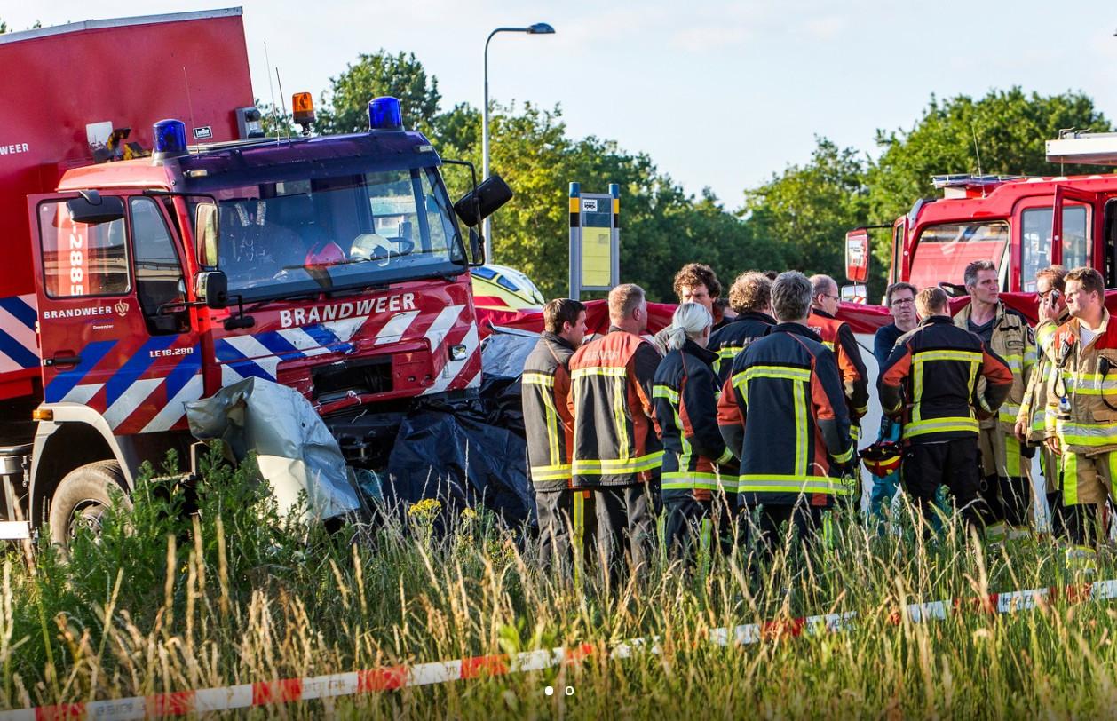 Brandweerlieden staan er verslagen bij na het dodelijke ongeluk op de Deventerweg in Deventer. Een personenauto en brandweerauto botsten op elkaar.