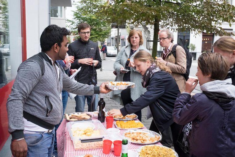 Bezoekers van Berchem Bazaar proeven van de gebakjes van bakkerij Sevli.