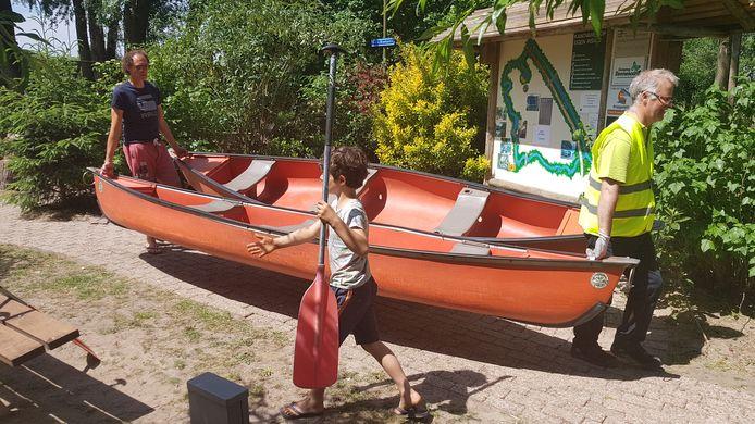 De gereinigde kano's worden naar de waterkant gebracht.