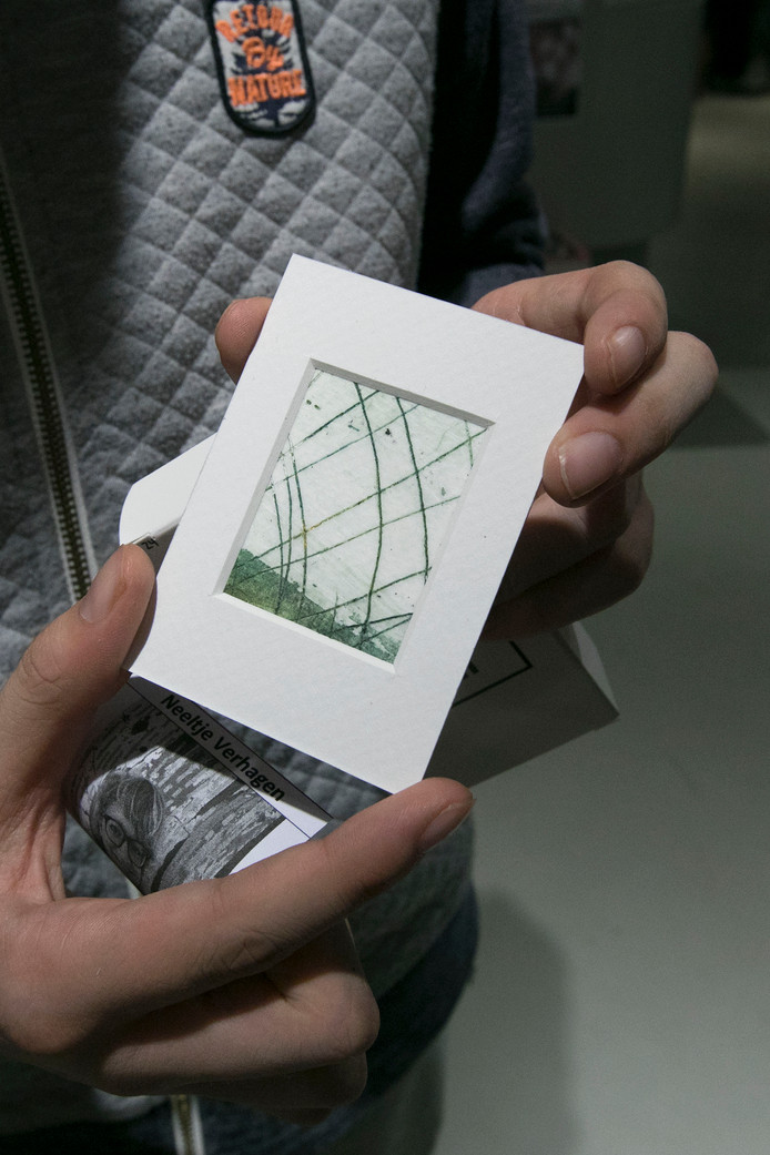 Pieter Habets trekt een pakje kunst uit de automaat.