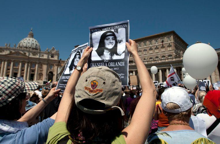 Demonstranten houden in 2012 tijdens een 'Mars voor gerechtigheid' bij het Vaticaan een foto van Emanuela Orlandi omhoog, om te protesteren tegen haar verdwijning in 1983.  Beeld AP