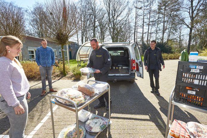Koks van Ezherwold Guido Schurink (r) en Bram Holland (m) laden samen met medewerkers van het leger Des Heils de luxe broodjes en salades uit.