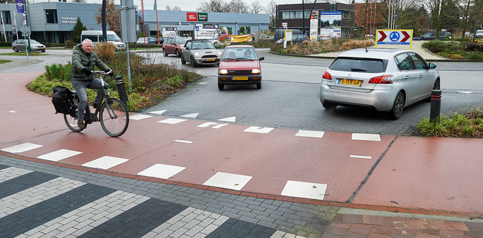 De onheilsplek op rotonde 't Kruispunt in Heesch. Op de plaats waar de man op de foto rijdt, werd woensdag een scholier geschept die de andere kant op fietste.