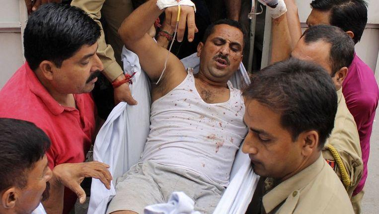 Een gewonde politieman wordt naar het ziekenhuis vervoerd na de aanval op het politiebureau Beeld reuters