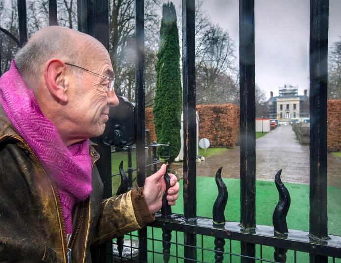 Jacob Snijders tuurt door het hek naar paleis Huis ten Bosch, dat eind dit jaar uit de steigers zou moeten zijn.