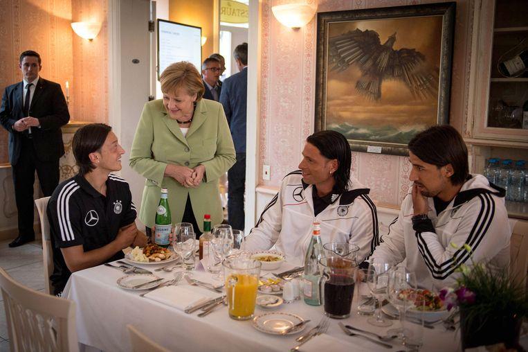 Het Duitse voetbalelftal ontmoet Bondskanselier Angela Merkel in Gdansk tijdens het EK Voetbal in 2012. Links Mesut Özil, rechts  voetballers Tim Wiese en Sami Khedira.  Beeld EPA