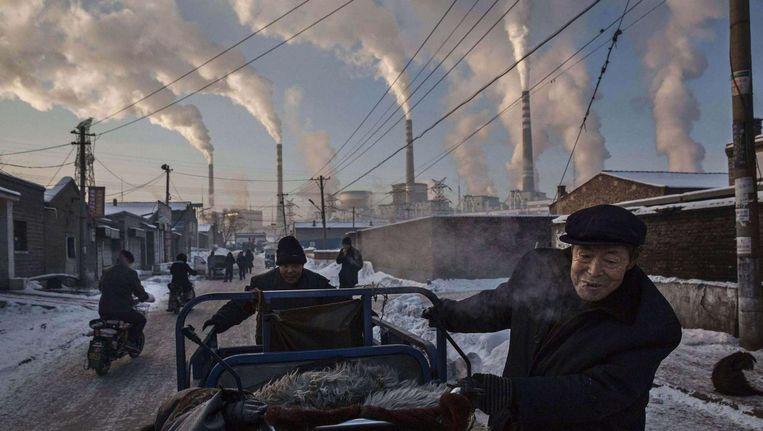 Mannen in een wijk in de Chinese provincie Shanxi, met op de achtergrond een kolencentrale. Beeld getty
