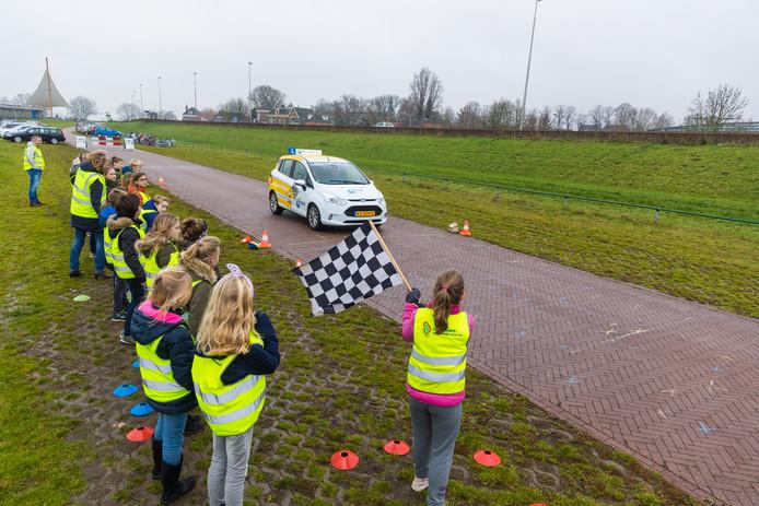 De groepen 5 en 6 van de Jan Jaspersschool onderzoeken de remweg van een auto. tijdens de ANWB-streetwise les bij de jachthaven in Hattem.