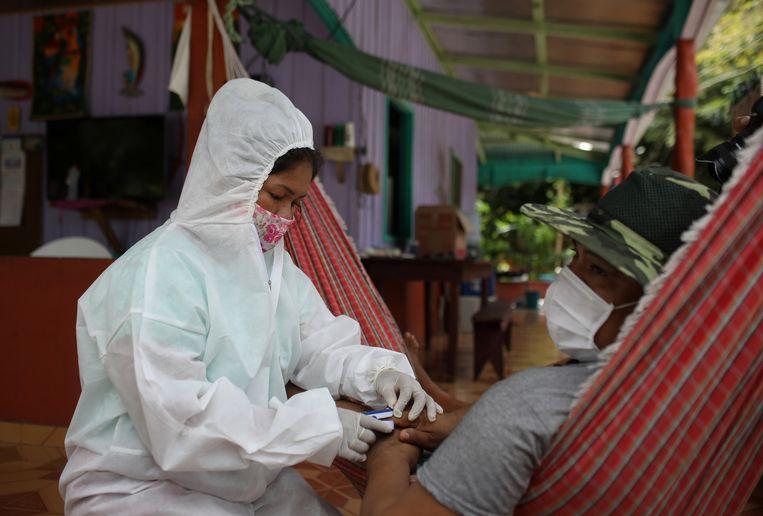 Een verpleegster meet het zuurstofgehalte in het bloed van Raimundo Cruz da Silva (42) in het dorpje Tres Unidos, in de staat Amazonas in Brazilië (21/05/2020).