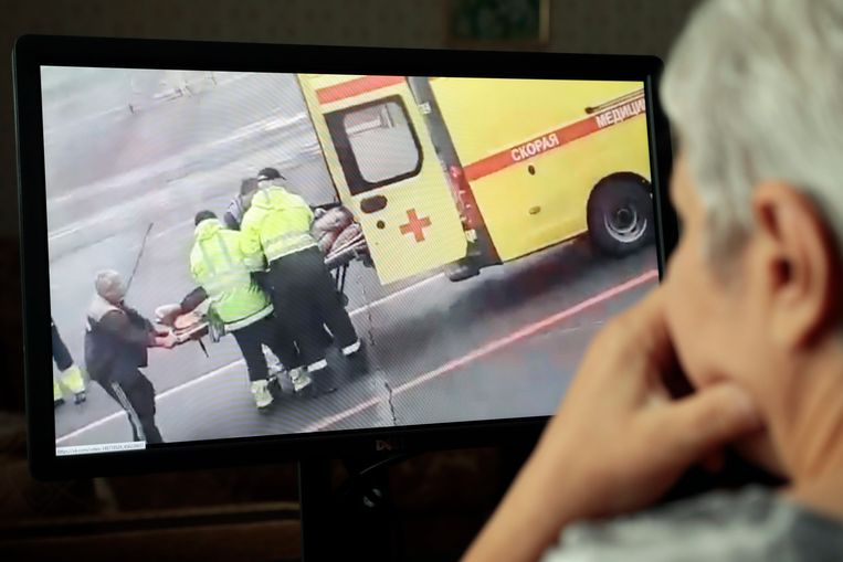 Iemand in Moskou bekijkt een video van hoe Navalny op een brancard een ambulance in wordt gedragen. Beeld Hollandse Hoogte / EPA